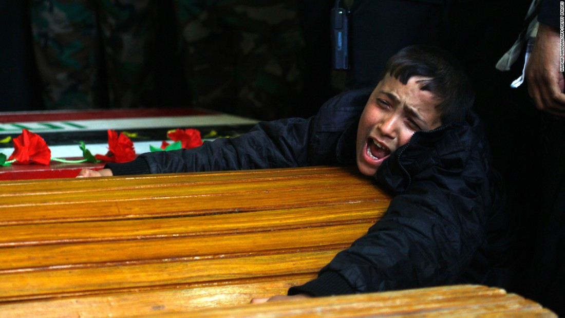 A boy mourns over his father's coffin during a funeral ceremony in Najaf, Iraq, on Wednesday, March 16. The boy's father was a Shiite fighter who was killed in Syria while battling the ISIS militant group.