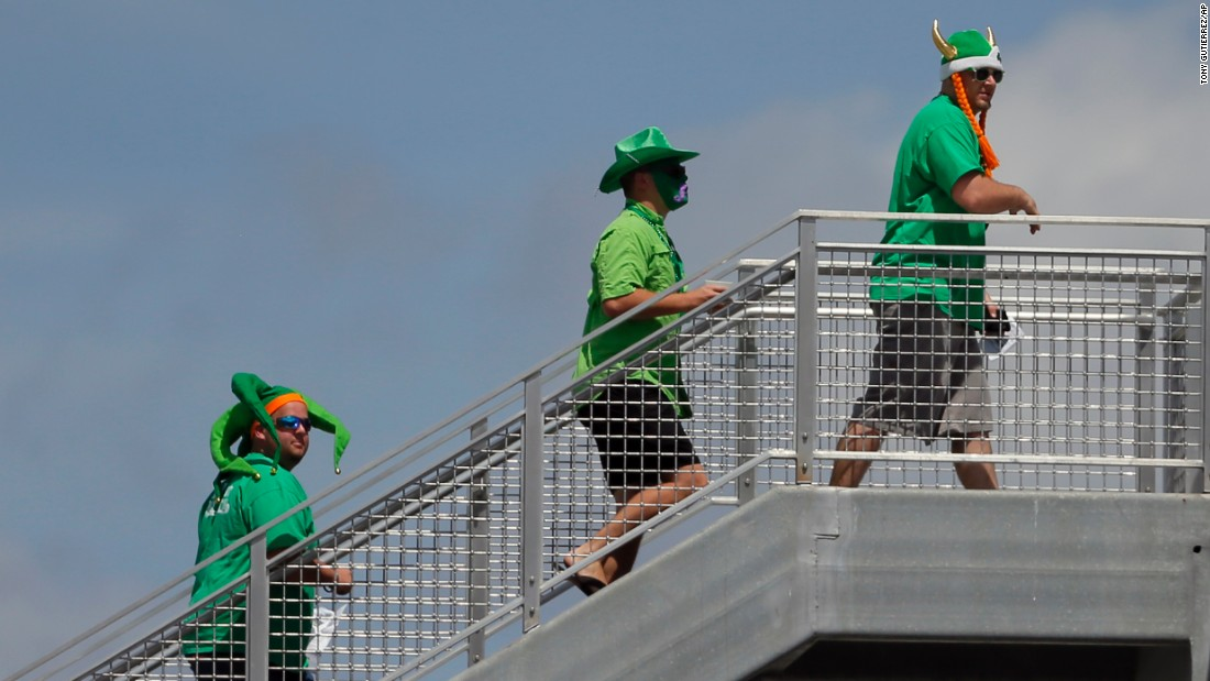 Three fans dressed in green walk up the stairwell to the roof of the Green Monster during the first inning of a spring training baseball game between the Baltimore Orioles and Boston Red Sox in Fort Myers, Florida.