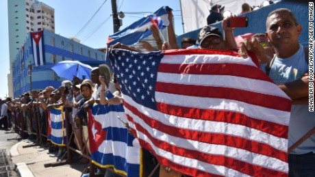 Cubans hold US and Cuban flags outside the US Embassy building as the US flag is raised over it in Havana on August 14, 2015, during US Secretary of State John Kerry's (out of frame) visit. The Marine guard of the newly reopened US embassy in Cuba raised the flag over the building Friday for the first time in 54 years, marking the end of the countries' Cold War standoff. AFP PHUOTO/Adalberto Roque        (Photo credit should read ADALBERTO ROQUE/AFP/Getty Images)