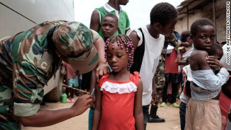 An Angolan military member gives a girl a yellow fever vaccine in Luanda, Angola, in February.