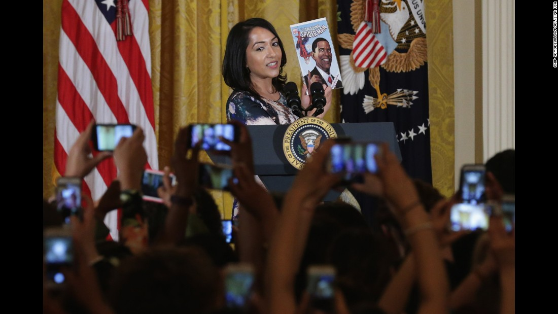 Sana Amanat, a comic book creator and editor, holds up a Spider-Man comic featuring President Barack Obama as she introduces him at a White House reception on Wednesday, March 16.