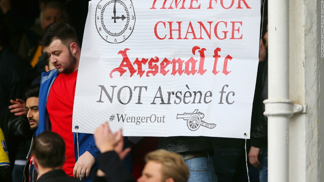 Despite Arsenal's 2-0 win, a disgruntled  Arsenal supporter holds a banner asking to replace manager Arsene Wenger after the Premier League match at Goodison Park on March 19, 2016 in Liverpool, England.