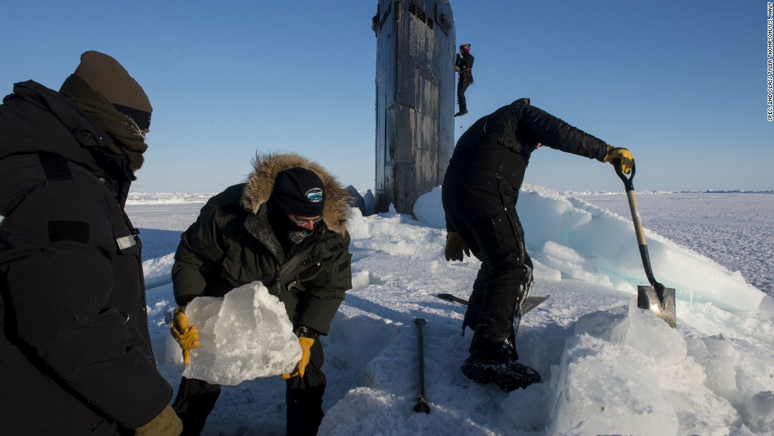 Sailors and civilians, assigned to Arctic Submarine Lab, clear the ice from the hatch of USS Hampton (SSN 767).