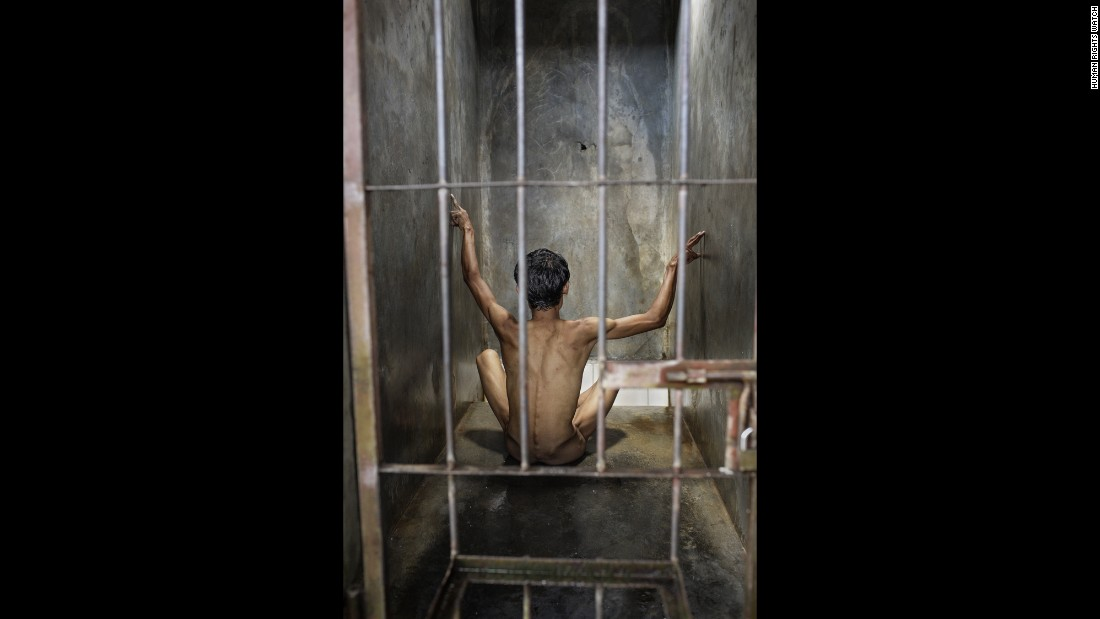 A man sings in his cell, his hands moving in an intricate dance, at Pengobatan Alternatif Jasono, a traditional healing center in Cilacap, Central Java.