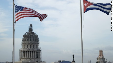 United States and Cuban flags fly side-by-side on the roof of the Iberostar Hotel Parque Central near El Capitolio (background) in the historic Old Havana neighborhood March 20, 2016 in Havana, Cuba.