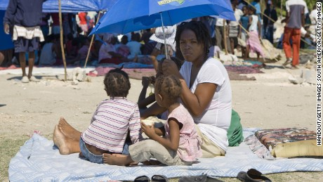 A mother shelters her children from the sun in a tent city in the commune of Cite Soleil after the earthquake in Haiti in 2010.
