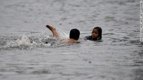 Children swim on a flooded street in Manila on September 23, 2013, after  monsoon rains and Typhoon Usagi caused floods and landslides.