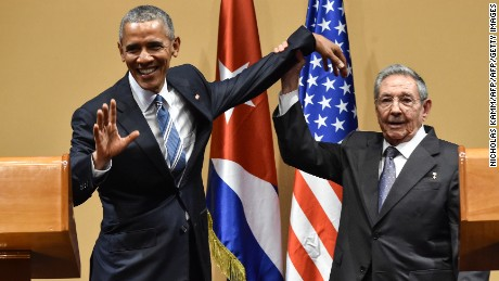 Cuban President Raul Castro (R) raises US President Barack Obama's hand during a meeting at the Revolution Palace in Havana on March 21, 2016.