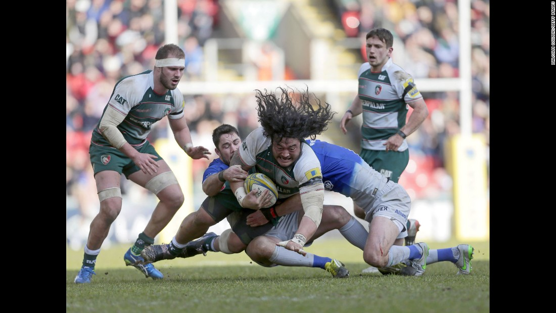 Logovi'i Mulipola, a rugby player with the Leicester Tigers, is tackled by Saracens players during a Premiership match in Leicester, England, on Sunday, March 20.