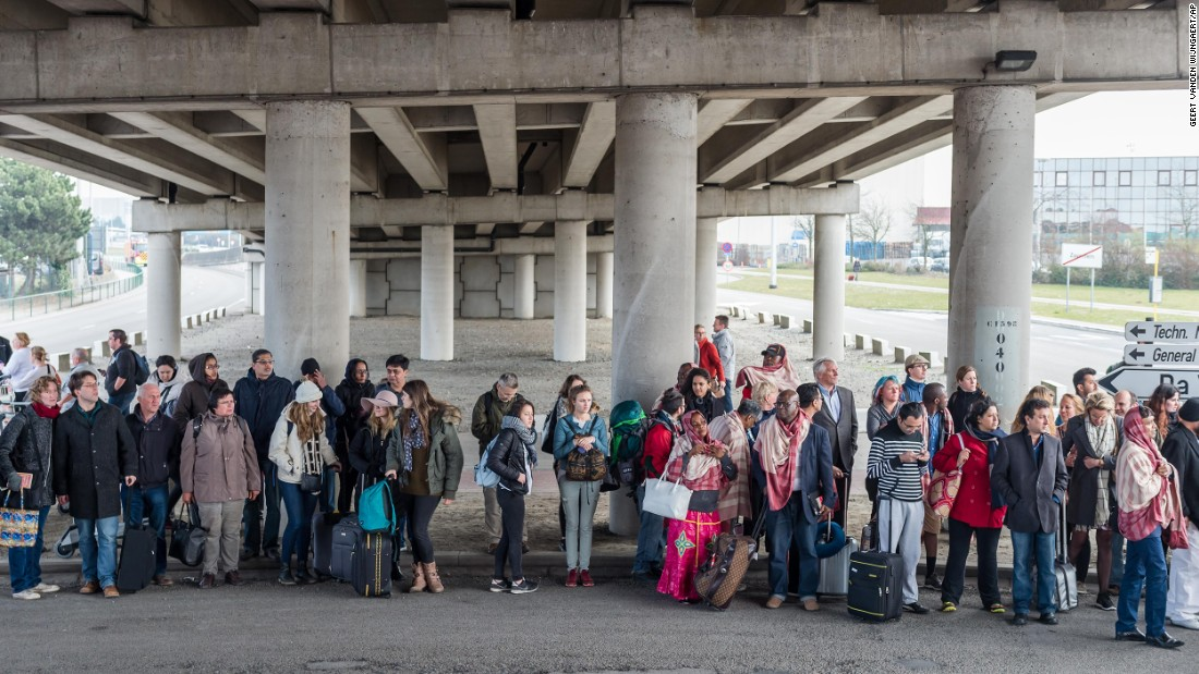 Passengers gather outside the airport.