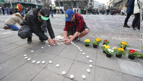 People leave candles and flowers in tribute to victims of triple bomb attacks in front of the stock exchange building in the city center of Brussels on Tuesday.