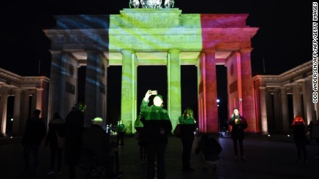 People make photos as the colors of the Belgian flag are projected on to the Brandenburg Gate in Berlin as the German capital shows its solidarity following the Brussels attacks on March 22, 2016. Security was tightened across Europe and transport links paralysed after a series of apparently coordinated explosions ripped through Brussels airport and a metro train, killing at least 34 people. / AFP / ODD ANDERSEN        (Photo credit should read ODD ANDERSEN/AFP/Getty Images)