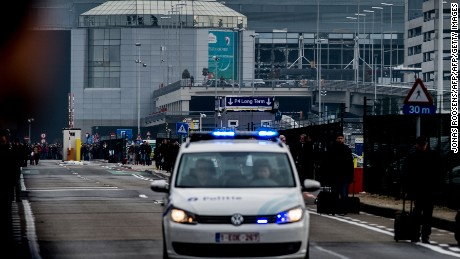 A picture taken on March 22, 2016 shows a Belgian police vehicle driving past passengers who are evacuating the Brussels Airport of Zaventem. At least 13 people were killed and 35 injured as twin blasts rocked the main terminal of Brussels airport on March 22, 2016, Belgian media quoted the federal prosecutor as saying. Officials were not immediately available to confirm the figure when contacted by AFP. The federal police earlier confirmed one death. / AFP / Belga / Jonas Roosens / Belgium OUT        (Photo credit should read JONAS ROOSENS/AFP/Getty Images)