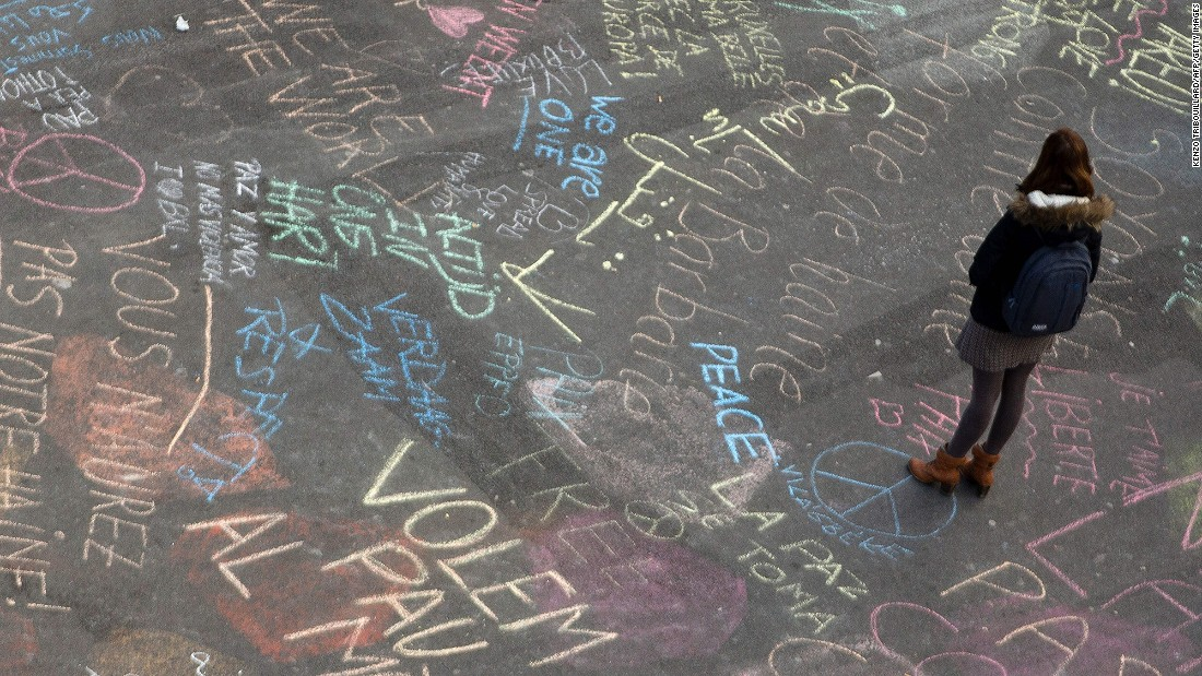 A woman reads messages written on the ground at Brussels' Place de la Bourse on March 22.
