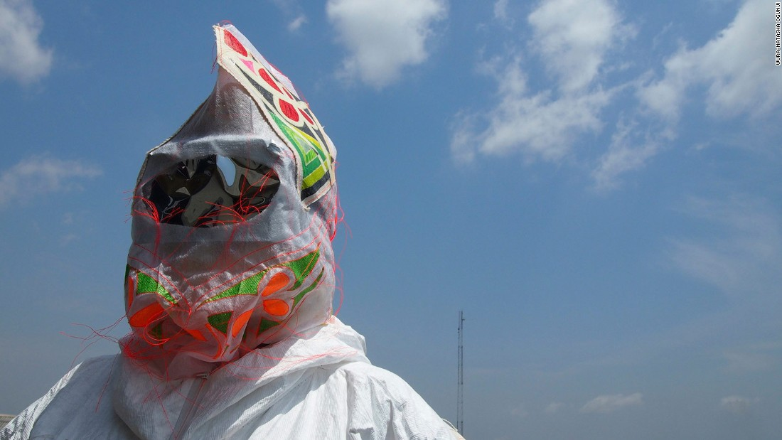 "The exhibition looks at masks as social commentary and critique. Pictured: A video still from the film ""An Ancestor Takes a Photograph"" (2014), filmed in Nigeria. Visual artist and performer Wura-Natasha Ogunji brings a troupe of women to the streets of Lagos to perform masquerade (a traditionally male enterprise) to challenge gender roles in Africa."