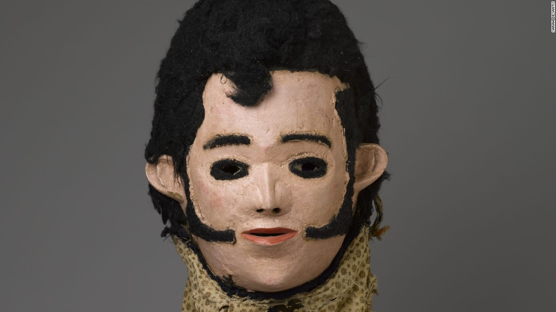 """Elvis Mask for Nyau Society"", Unidentified Chewa artist (c. 1977). This wooden mask is from the Nyau Society, Malawi, whose masks represent spirits of the dead, wild bush spirits and caricatures of outsiders like Swahili slave traders, the Virgin Mary, and  iconic foreigners such as Elvis Presley."