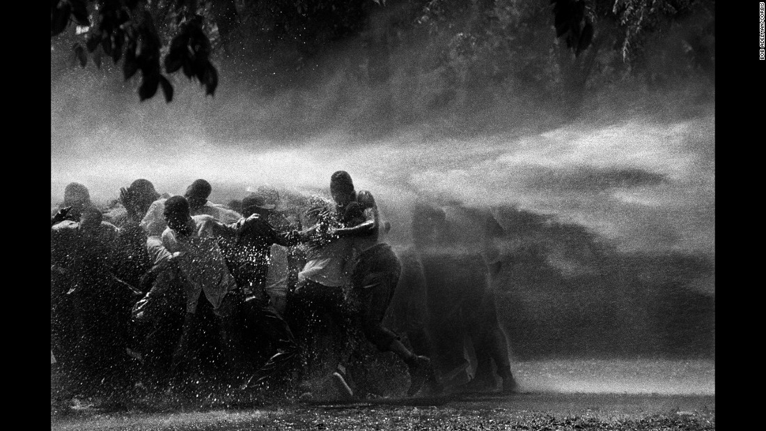 "Civil rights demonstrators are sprayed with water in Birmingham, Alabama, in 1963. ""I have never witnessed such cruelty,"" Adelman said. ""There was almost as much moisture behind the lens as in front. I gave a print of this picture to Dr. King. He studied it and said, 'I am startled that out of so much pain some beauty came.' """