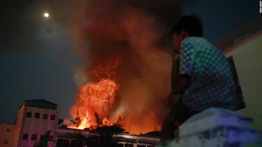 A boy watches a fire at a market in Mandalay, Myanmar, on Tuesday, March 22. Firefighters from all over Mandalay worked to extinguish the blaze.