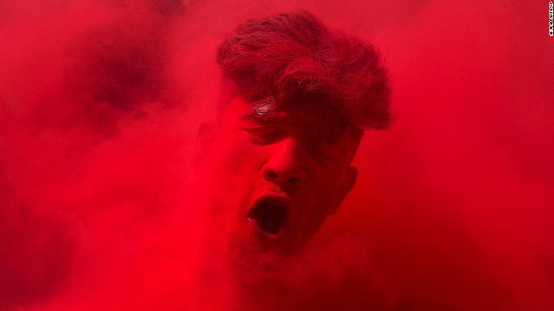 A reveler's face is smeared with colored powder as he dances during Holi celebrations in Gauhati, India, on Thursday, March 24. The Holi festival of colors is a Hindu celebration marking the arrival of spring.