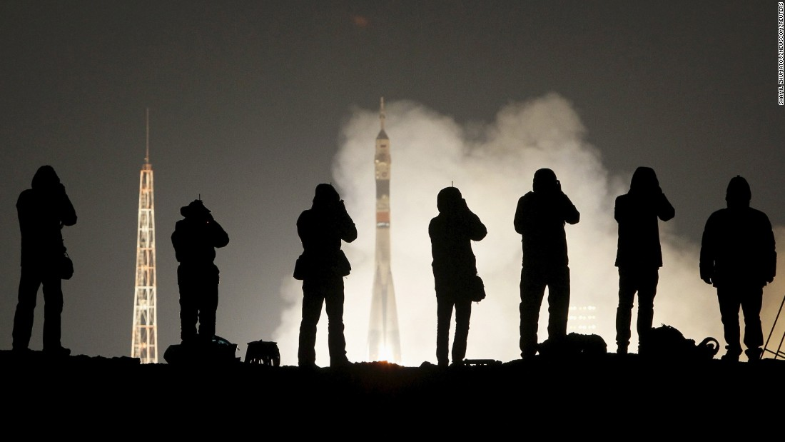 Photographers take pictures of a Soyuz rocket on Saturday, March 19, as it takes off from Kazakhstan carrying three astronauts to the International Space Station.