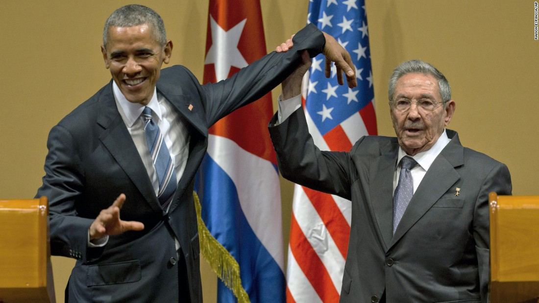 Cuban President Raul Castro tries to lift up the arm of U.S. President Barack Obama at the end of a joint news conference in Havana, Cuba, on Monday, March 21.