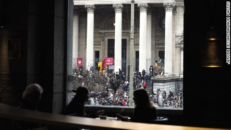 BELGIUM. Brussels. March 23, 2016.People gathering in front of la Bourse of Brussels.Two blasts hit Brussels Airport (Zaventem) on March 22 morning, another one struck the Maelbeek metro station an hour later, in the European district.20 people died at the Maelbeekmetro station and10died at the airport, more than 100 peolple were injured.Belgium has now raised its terror threat to its highest level (Level 4).