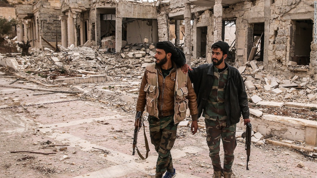 Syrian soldiers survey the damage to a villa belonging to the Qatari royal family on March 25. The villa near Palmyra served as an ISIS headquarters after being abandoned by its owner.