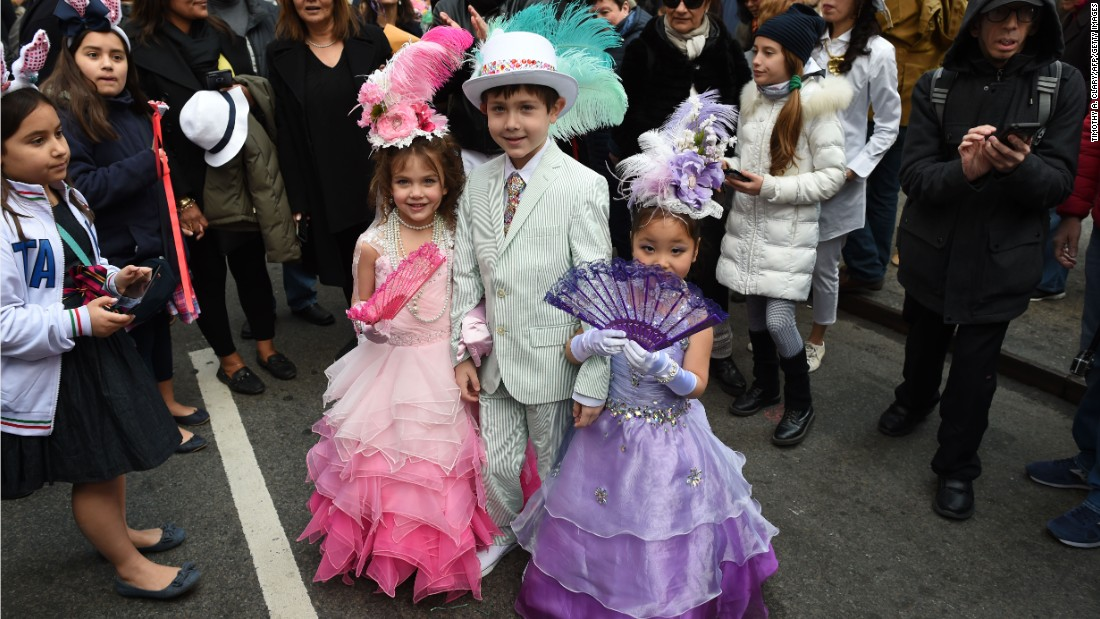 Children show off their Easter finery as a crowd looks on.