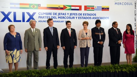 (L to R): Chile's President Michelle Bachelet, Uruguay's Tabare Vazquez, Argentina's Mauricio Macri, Paraguay's Horacio Cartes, Brazil's Dilma Rousseff, Bolivia's Evo Morales, Guyana's PM Moses Nagamootoo and Venezuelan Foreign Minister Delcy Rodriguez pose for the family photo of the 49th Summit of Presidents of the Mercosur in Luque, Paraguay, on December 21, 2015. AFP PHOTO/ NORBERTO DUARTE / AFP / NORBERTO DUARTE        (Photo credit should read NORBERTO DUARTE/AFP/Getty Images)