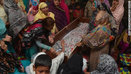 "Pakistani relatives mourn over the body of a victim during a funeral following an overnight suicide bombing in Lahore on March 28, 2016.  The toll from a suicide blast in Pakistan's Lahore rose to 69, officials said on March 28, as authorities hunted for the ""savage inhumans"" behind the attack in a park packed with Christian families celebrating Easter Sunday. More than 200 people were injured, many of them children, when explosives packed with ball bearings ripped through crowds near a children's play area in the park in Lahore, leaving dozens dead or bloodied. / AFP / ARIF ALI        (Photo credit should read ARIF ALI/AFP/Getty Images)"