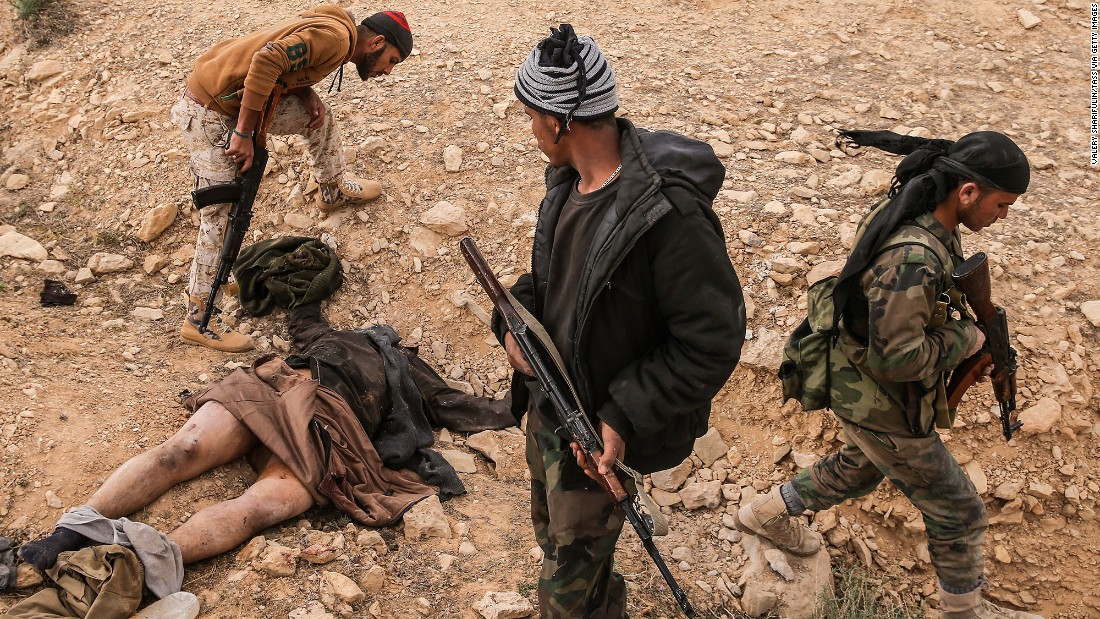 Syrian soldiers stand near the body of an ISIS militant near Palmyra on Friday, March 25.