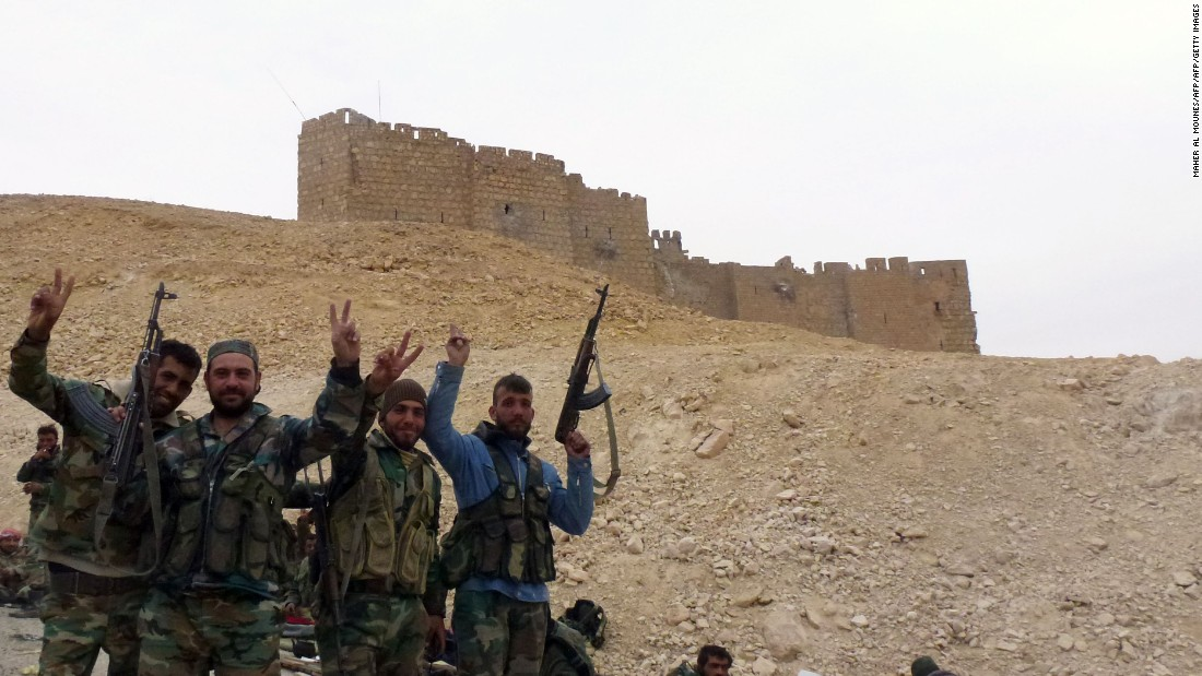 Syrian pro-government forces gesture next to the Palmyra citadel.