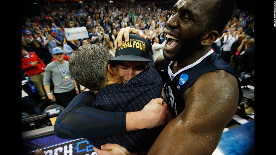 Daniel Ochefu, right, embraces Villanova teammate Ryan Arcidiacono as Arcidiacono hugs head coach Jay Wright on Saturday, March 26. The Wildcats had just defeated Kansas 64-59 in the Elite Eight of the NCAA Tournament.