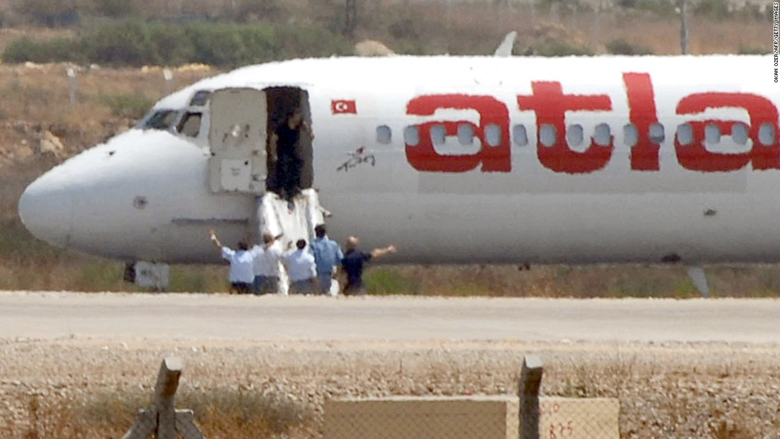 Unidentified men stand by a hijacked Turkish airplane Atlasjet during the surrender of its two hijackers at Antalya Airport in August 2007. The two men who hijacked the Turkish airplane and forced it to land in southern Turkey surrendered, a Turkish official said.