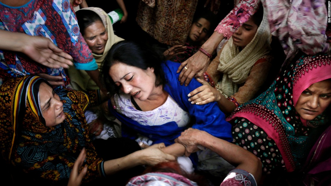 Women in Lahore try to comfort a mother who lost her son in the attack.
