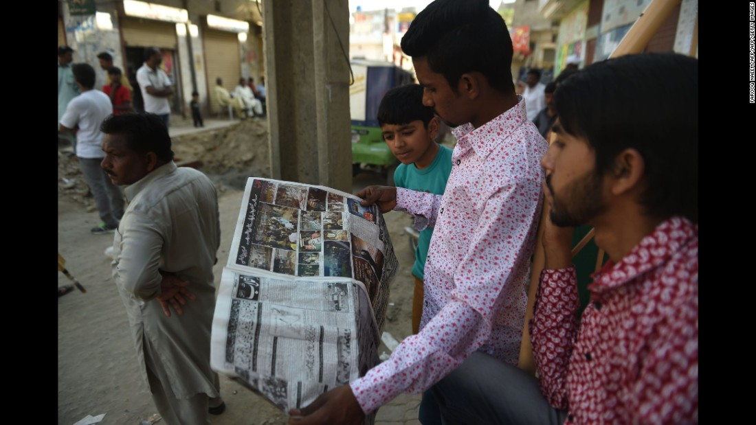 Men in Lahore read the newspaper a day after the deadly blast.