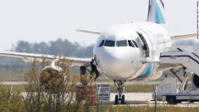 A man climbs out of the cockpit window an EgyptAir Airbus A-320 parked at the tarmac of Larnaca airport after being hijacked and diverted to Cyprus on March 29, 2016.  The hijacker who seized the Egyptian airliner and forced it to land in Cyprus has been detained, Cypriot government spokesman Nicos Christodoulides said. / AFP / BEHROUZ MEHRI        (Photo credit should read BEHROUZ MEHRI/AFP/Getty Images)