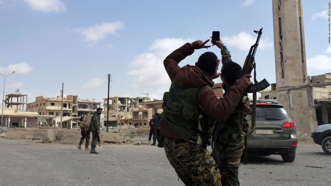 "Syrian troops take a selfie as they walk in the damaged streets of Palmyra, Syria, on Sunday, March 27. <a href=""http://www.cnn.com/2016/03/27/world/gallery/retaking-palmyra/index.html"" target=""_blank"">They had just recaptured Palmyra from ISIS,</a> months after the city fell to the Islamic extremist group, state media reported."