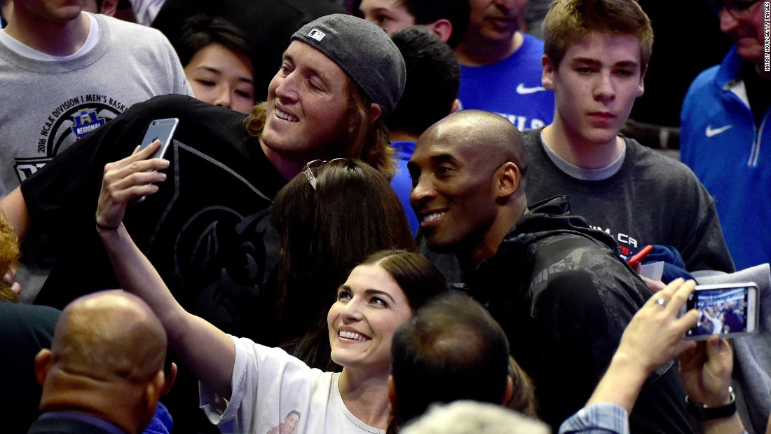 NBA star Kobe Bryant smiles for a fan's selfie as he watches an NCAA Tournament game in Anaheim, California, on Thursday, March 24.