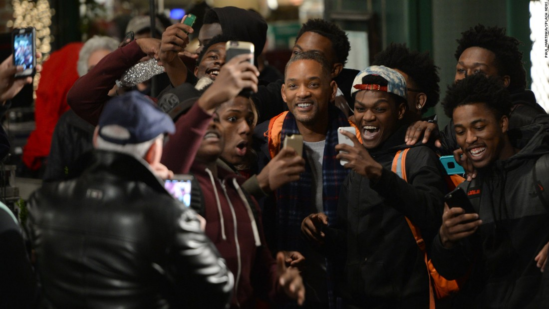 "People in Brooklyn, New York, take out their phones to get photos with actor Will Smith on Wednesday, March 23. Smith was filming ""Collateral Beauty"" there."