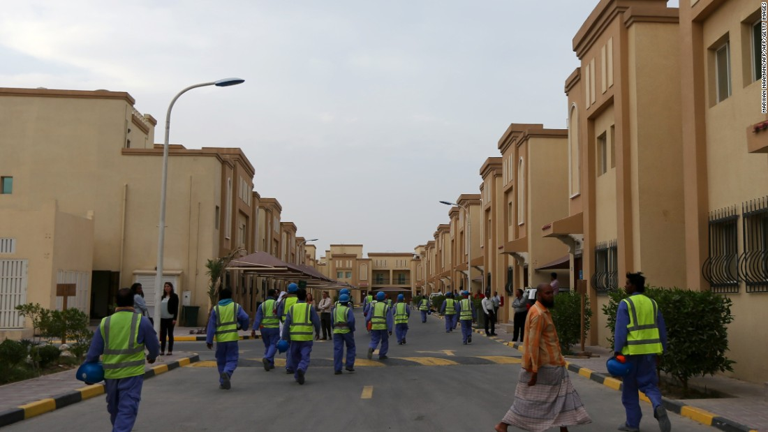 Foreign laborers working on the construction site of the al-Wakrah football stadium, one of Qatar's World Cup venues, walk back to their accommodation compound after a working day in May 2015.