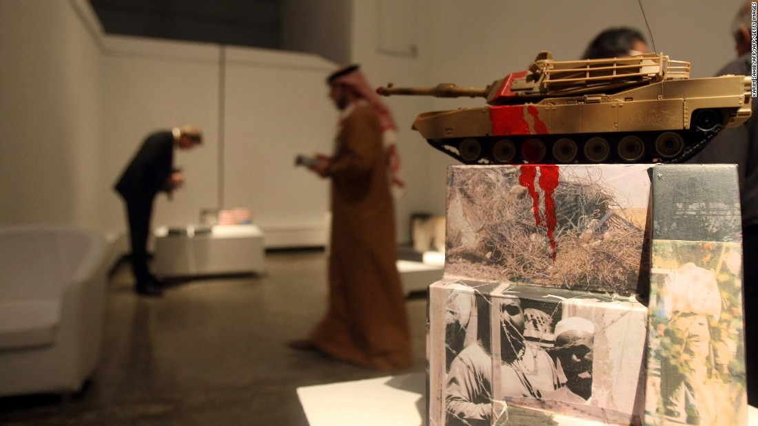 "Visitors look at an artwork entitled ""The Ugly Face of Occupation 2009"" by Iraqi artist Dia Azzawi displayed at ""My Home Land"" exhibition in Dubai in 2010. Seven Iraqi artists living outside Iraq took part in the exhibition."