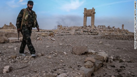 A Syrian government army soldier walks near the ruins of the temple of Baal Shamin destroyed by ISIS militants in Palmyra, a UNESCO world heritage site.