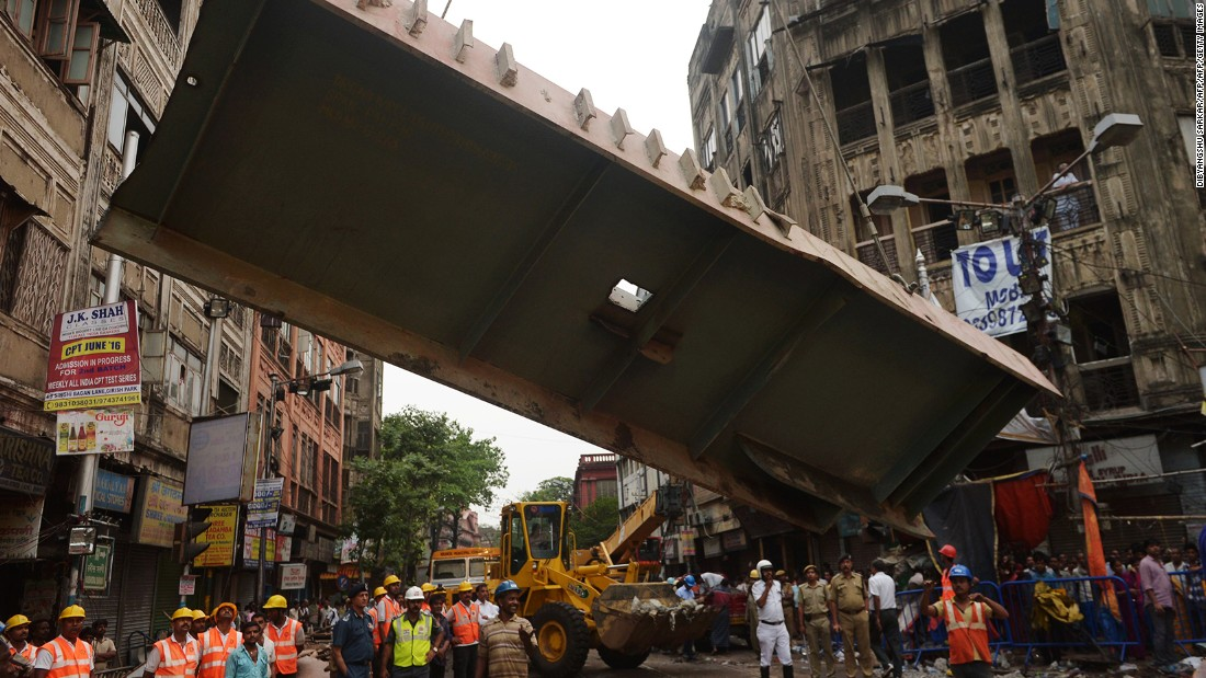 Workers remove a section of the collapsed overpass on Friday, April 1.