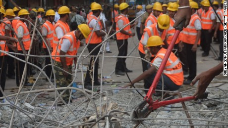 Indian rescue workers cut rebar and clear debris while looking for people trapped under the wreckage.