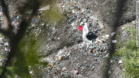 A forensic examiner searches for human remains below a garbage-strewn hillside in the densely forested mountains on the outskirts of Cocula, Mexico, on October 28, 2014. Suspects arrested earlier this week told prosecutors that many of the 43 students who disappeared on September 26 from Iguala had been held near this location. Mexico recoiled in fresh horror Tuesday over the discovery of yet another mass grave, in the futile month-long search for 43 missing college students. AFP PHOTO/ JESUS GUERRERO        (Photo credit should read JESUS GUERRERO/AFP/Getty Images)