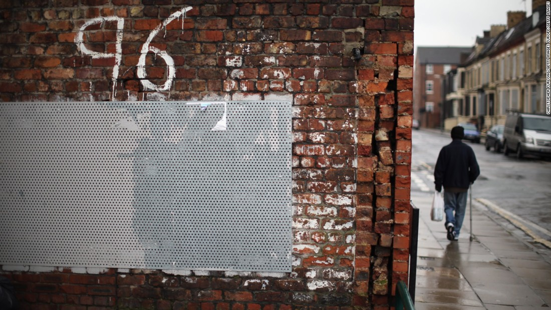 "A man walks past ""Justice for the 96"" graffiti near Anfield soon after the High Court quashed verdicts of accidental death on December 19, 2012. New inquests into the disaster were ordered."