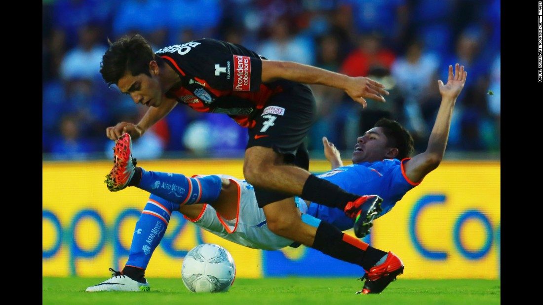 Cruz Azul's Kevin Montano slides into Pachuca's Rodolfo Pizarro during a league match in Mexico City on Saturday, April 2.