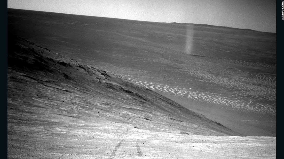 From its perch high on a ridge, Opportunity recorded this image of a Martian dust devil twisting through the valley below. Just as on Earth, a dust devil is created by a rising, rotating column of hot air. When the column whirls fast enough, it picks up tiny grains of dust from the ground, making the vortex visible.