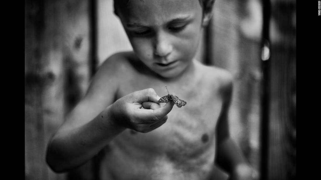 "Tharin, the son of photographer Tytia Habing, inspects a moth they found by the pool. Habing has been photographing Tharin as he explores their farm in rural Illinois. ""I hope people will look at (the photos) and remember that kids need to be outside,"" she said."